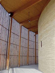 Působivý příklad nabíjené hliněné stěny v interiéru. Stěna v oblouku kopíruje vnější obrys budovy a nechává vyniknout svou strukturu.