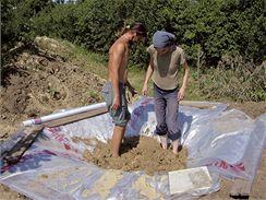 Ručně a nožně se chystá hlína na stavbu domu.