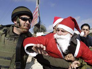 Ježíšovo rodiště: nepokoje i o Vánocích. Izraelský policista zasahuje proti palestinským demonstrantům, z nichž jeden je oblečen jako Santa Claus.