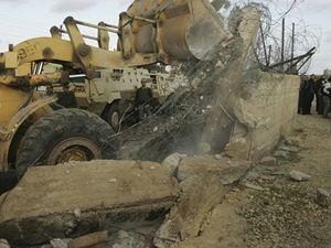Palestinský buldozér probourává hraniční bariéru do Egypta.