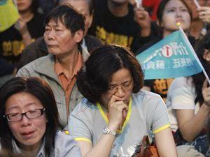 Příznivci vládního kandidáta pozorují výsledky se slzami v očích.