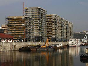 Holešovické doky. Na místě dřívějšího přístavu rostou domy pro více než tři tisíce lidí. Cena za bydlení v centru u řeky bude i nadále stoupat, jde tedy o vynikající investici.