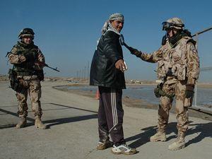 Příslušnice českého kontingentu v Iráku kontroluje iráckého pracovníka vojenské základny v Basře. (ilustrační foto)