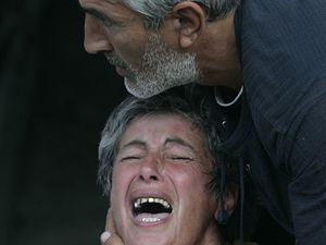 Plačící gruzínskou ženu utěšuje manžel, poté, co zjistila, že její dítě bylo zabito v sousedním městě Gori.
