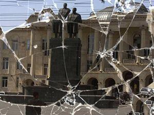 Odraz Stalinovy sochy ve výloze zničeného obchodu v gruzínském Gori