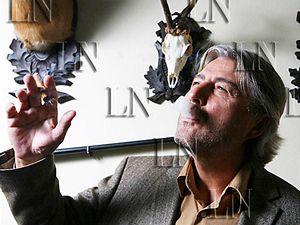 Bohumír Ďuričko v kanceláři svého hotelu Axa před loveckými trofejemi s whisky a doutníkem v ruce.