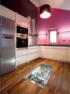Na pozadí tmavě šedé stěny kombinované s fialovou skvěle vynikne lakovaný bílý povrch dvířek kuchyňské linky. Ten navíc odráží světlo vstupující do místnosti střešními okny. Vyvýšené pódium umožnilo vytvoření zajímavého prvku v podlaze.
