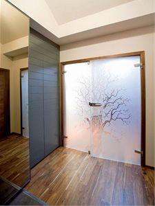 Ve vstupní hale určitě zaujmou prosklené dveře z mléčného skla zdobené dekorem stromu.
