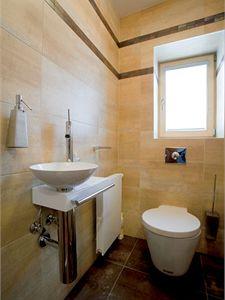 Střídmě a účelně zařízenou toaletu proteplují jemné barvy obkladů a měkce zaoblené tvary nábytku sanity a baterií. Obklady a keramické dlažby dodala firma Keramika Bílá Hora.