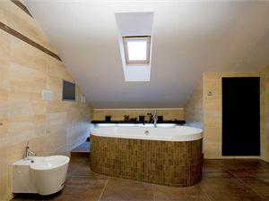 Koupelně dominuje samostatně stojící vana. Vana i baterie jsou návrhy designéra Philippe Starcka.