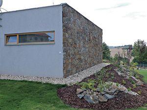 Ze severní strany dům chrání kamenná stěna z pískovců vytěžených v nedalekém lomu.