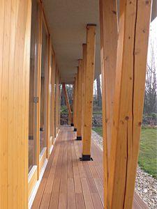 Krytá dřevěná terasa obepíná stavbu ze západní i jižní strany a vytváří přirozenou spojnici mezi domem a zahradou.