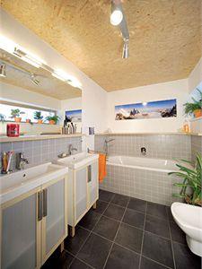 Do decentní koupelny v šedých a oranžových tónech přivádí denní světlo horizontální okno na východní straně.