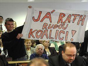 Demonstranti reagují s transparentem na slib Davida Ratha na ustavujícím zasedání středočeského zastupitelstva, které se sešlo 24. listopadu v Praze.