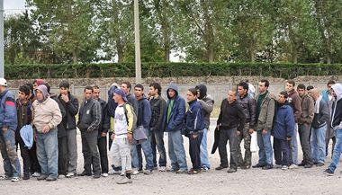 Uprchlíci stojí ve frontě na jídlo poskytované charitativní organizací ve francouzském Calais