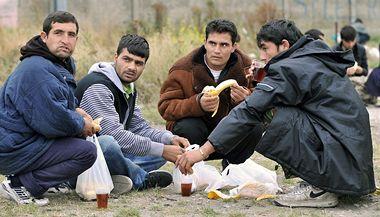 Uprchlíci večeří potraviny přidělené charitativní organizací ve francouzském Calais