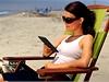 Čtenářka elektronických knih na pláži