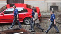Ingr v doprovodu policistů opouští budovu soudu..