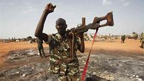 Sudanese military, holding a weapon, gestures during the visit of Sudanese President Omar al-Bashir in Heglig