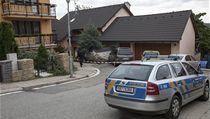 Novináře udržovala policie v dostatečné vzdálenosti od domu.