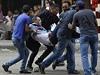 Demonstranti nesou zraněného muž. Při protestech v Káhiře dnes podle...