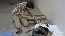 Muž ošetřuje chlapce zasaženého chemickým útokem