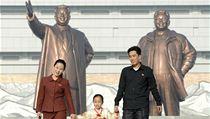 Severokorejská rodina. Na pozadí usměvavé sochy Kim Ir-sena a Kim Čong-ila