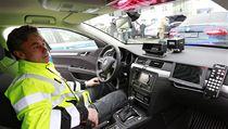 Policista sedí v jednom ze sedmi nových superbů, který dopravní policie převzala od automobilky Škoda Auto.