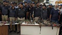 Pákistánská policie ukazuje výzbroj a mrtvá těla teroristů, kteří zaútočili na letiště v Karáši.