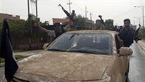Džihádisté ze sítě ISIL oslavují dobytí Mosulu. Z auta, které ukořistili uprchlým iráckým vojákům, vlaje černá vlajka.