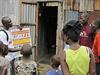 Muž podává obyvatelům informace o příznacích nákazy ebolou.