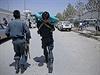 Sebevražedný útok v Afghánistánu, srpen 2014 - afghánský policista odnáší zraněného obyvatele Kábulu.