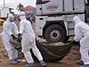 Zdravotníci v ochranných oblecích přenášejí tělo člověka zemřelého na ebolu (Monrovia, Libérie).