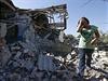Žena prochází domem zničeným během bojů o Mariupol.