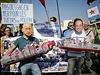 Demonstruj�c� s maskami rusk�ho a francouzsk�ho prezidenta protestuj� proti...