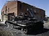 Válka na Ukrajině: vypálený tank ukrajinské armády u zničené budovy dětské školky ve vsi Kominternove.