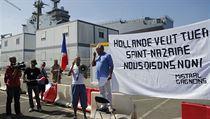 """Demonstrace za podporu prodeje Mistralů Rusku. Na transparentu stojí: Hollande chce zničit přístav Les Chantiers de l'Atlantique, my říkáme """"NE""""."""