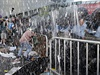 Protestující se drží plotu, zatímco kolem něj prší slzný plyn.