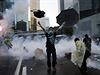 Protestující v Hongkongu s deštníkem. Kolem zuří bitva mezi policií a demonstranty.