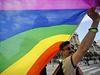 Aktivista za práva homosexuálů nese vlajku během pochodu v srbském Bělehradu.