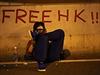 """Demonstrant v plynové masce sedí u nápisu """"Svobodný Hongkong"""". Kvůli častému nasazování slzného plynu už lidé masky často ani nesundávají."""