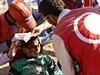 Turečtí zdravotníci ošetřují zraněného syrského chlapce.