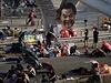 """Demonstranti odpočívají v ulicích Hongkongu. Na sloupu visí """"vylepšený"""" portrét předsedy výkonné rady Hongkongu Leung Čchun-jinga."""