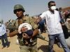 Turecký voják přenáší dítě kurdských běženců ze syrského města Kobani, na které útočí islamisté z Islámského státu.