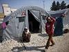 Kurdští uprchlíci ze Sýrie sedí u stanů na hranicích s Tureckem.