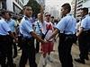 Policejní kordon brání střetu prodemokratických aktivistů a jejich odpůrců. Jedním z kritiků okupace centra města je i muž uprostřed, v triku s vlajkou ČLR.