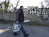 Ukrajinský volební komisař s urnou kráčí kolem domů, zničených během občanské války.