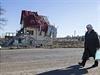 Povolební ostřelování Donbasu. Žena kráčí podél zničeného domu.