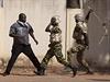 Improvizovaná zbraň. Dvojice vojáků zasahuje proti protivládnímu demonstrantovi.