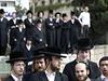 Ortodoxní Židé přihlížejí na místě činu po útoku palestinského útočníka.